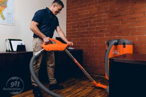 restoration professional extracting water from office